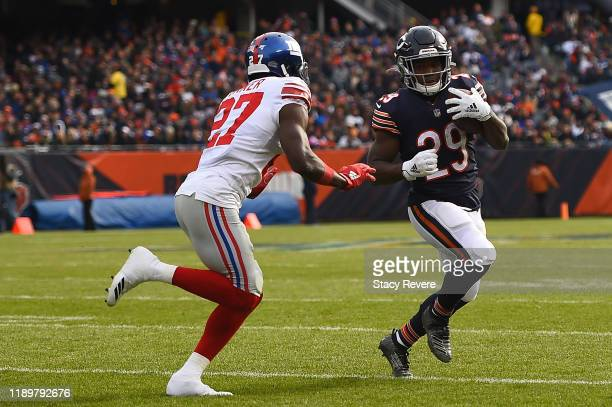 Tarik Cohen of the Chicago Bears is pursued by Deandre Baker of the New York Giants during the first half at Soldier Field on November 24 2019 in...