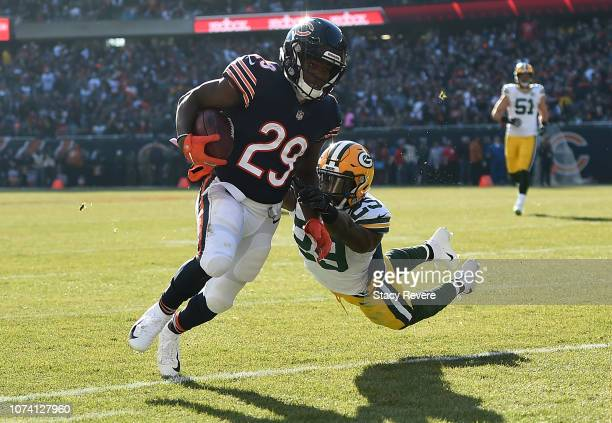 Tarik Cohen of the Chicago Bears runs the football against Kentrell Brice of the Green Bay Packers at Soldier Field on December 16 2018 in Chicago...