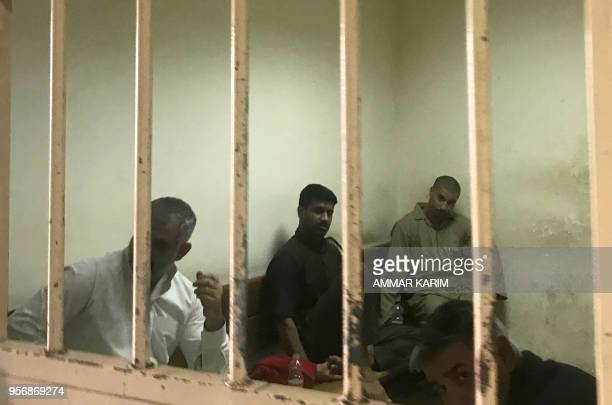 Tarik Jadaoun known by his nom de guerre Abu Hamza alBeljiki sits inside a cell at a court in Baghdad on May 10 2018 An Iraqi court today began the...