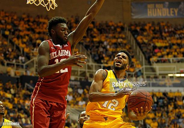 Tarik Phillip of the West Virginia Mountaineers drives to the basket against Khadeem Lattin of the Oklahoma Sooners during the game at the WVU...