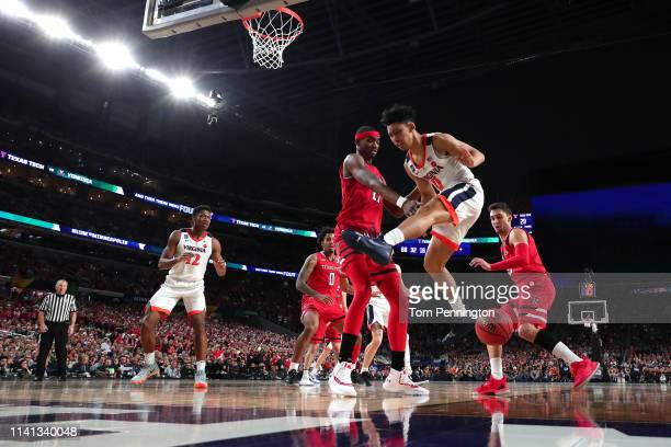 Tariq Owens of the Texas Tech Red Raiders and Kihei Clark of the Virginia Cavaliers battle for the ball in the first half during the 2019 NCAA men's...
