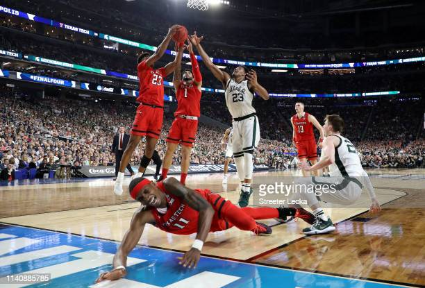 Tariq Owens of the Texas Tech Red Raiders falls on the court as Xavier Tillman of the Michigan State Spartans battles for the ball with Jarrett...