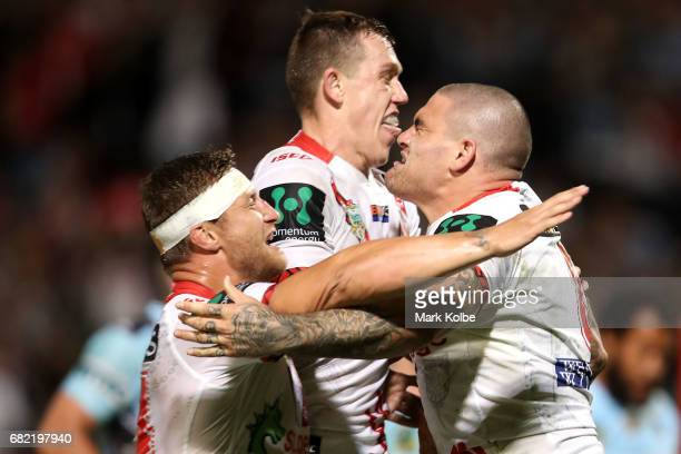 Tariq Sims and Cameron McInnes of the Dragons celebrate with Russell Packer of the Dragons as he celebrates scoring a try during the round 10 NRL...