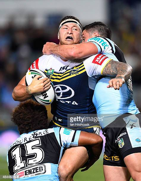 Tariq Sims of the Cowboys is tackled by Junior Roqica and Chris Heighington of the Sharks during the round 25 NRL match between the North Queensland...