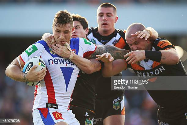Tariq Sims of the Knights is tackled by the Tigers defence during the round 23 NRL match between the Wests Tigers and the Newcastle Knights at...