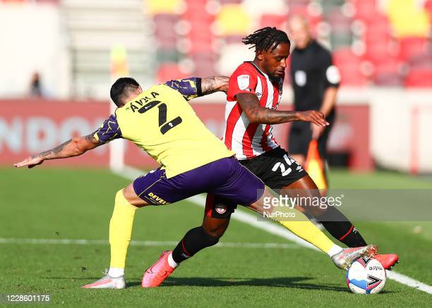 Tariqe Fosu of Brentford battling for possession with Pipa of Huddersfield Town during the Sky Bet Championship match between Brentford and...