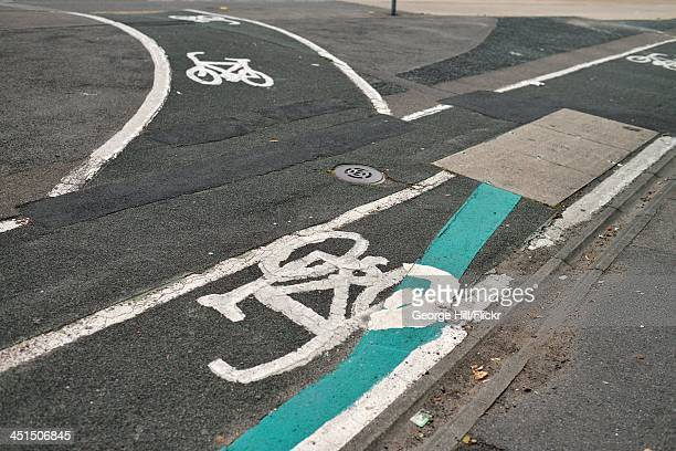 Tarmac road surface with cycle lane indicators and white hand-painted bicycle icons.