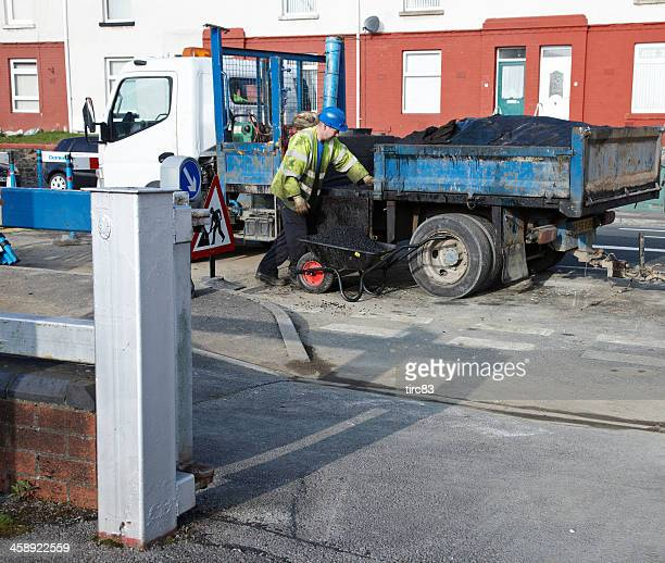 Tarmacadam Arbeiter laden Heißer asphalt in Schubkarre