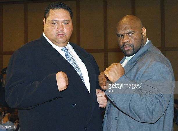 Taro Akebono Japan's first foreignborn sumo grand champion and American K1 fighter Bob Sapp make a fighting pose during a news conference at a Tokyo...