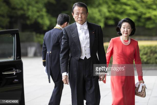 Taro Aso Japan's deputy prime minister and finance minister left and Chikako Aso his wife arrive for Emperor Naruhito's ascension ceremony at the...