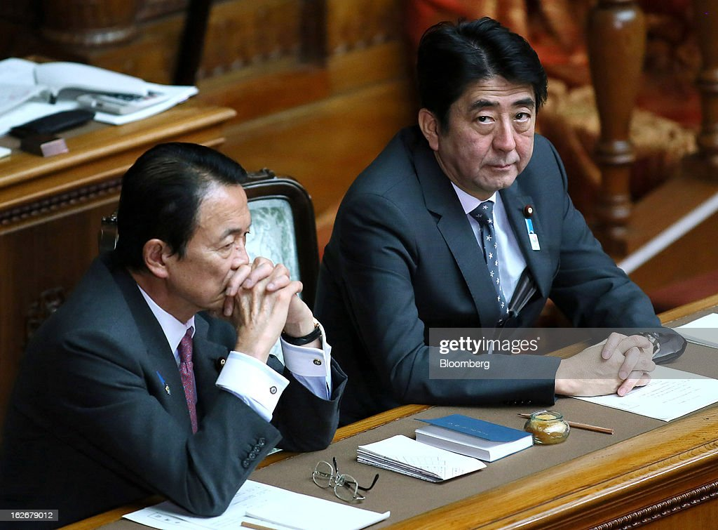 Taro Aso, Japan's deputy prime minister and finance minister, left, and Shinzo Abe, Japan's prime minister, attend a plenary session at the upper house of the parliament in Tokyo, Japan, on Tuesday, Feb. 26, 2013. Abe's policies aimed at ending deflation could distort trade, drive up asset prices in other nations and lead to global financial instability, according to HSBC Holdings Plc. Photographer: Haruyoshi Yamaguchi/Bloomberg via Getty Images