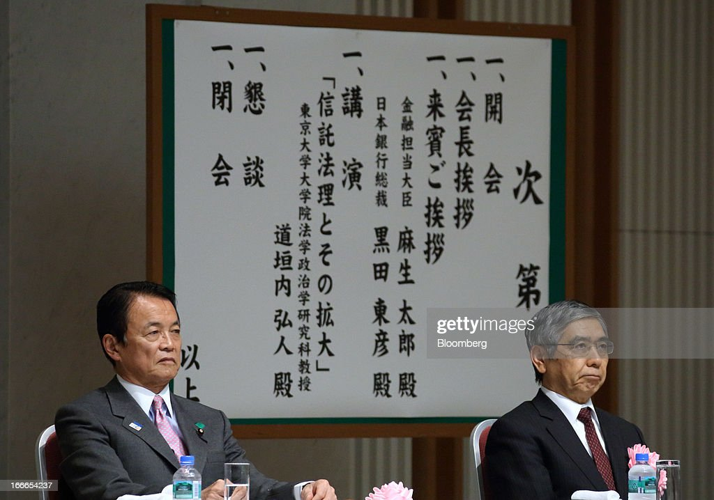 Taro Aso, Japan's deputy prime minister and finance minister, left, and Haruhiko Kuroda, governor of the Bank of Japan (BOJ), attend the annual meeting of the Trust Companies Association of Japan in Tokyo, Japan, on Monday, April 15, 2013. Kuroda reiterated today that he has a two-year time horizon in mind for achieving his inflation goal. He will also speak today at the annual meeting. Photographer: Tomohiro Ohsumi/Bloomberg via Getty Images