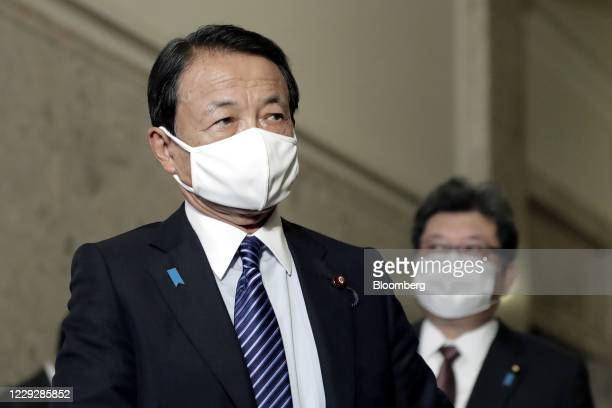 Taro Aso, Japan's deputy prime minister and finance minister, left, wears a protective face mask as he arrives for an extraordinary session at the...