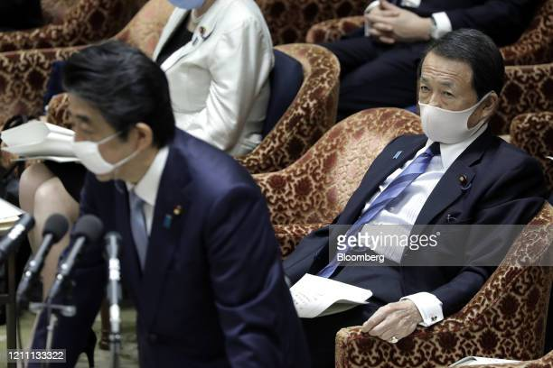 Taro Aso, Japan's deputy prime minister and finance minister, right, wears a protective mask as he looks on while Shinzo Abe, Japan's prime minister,...