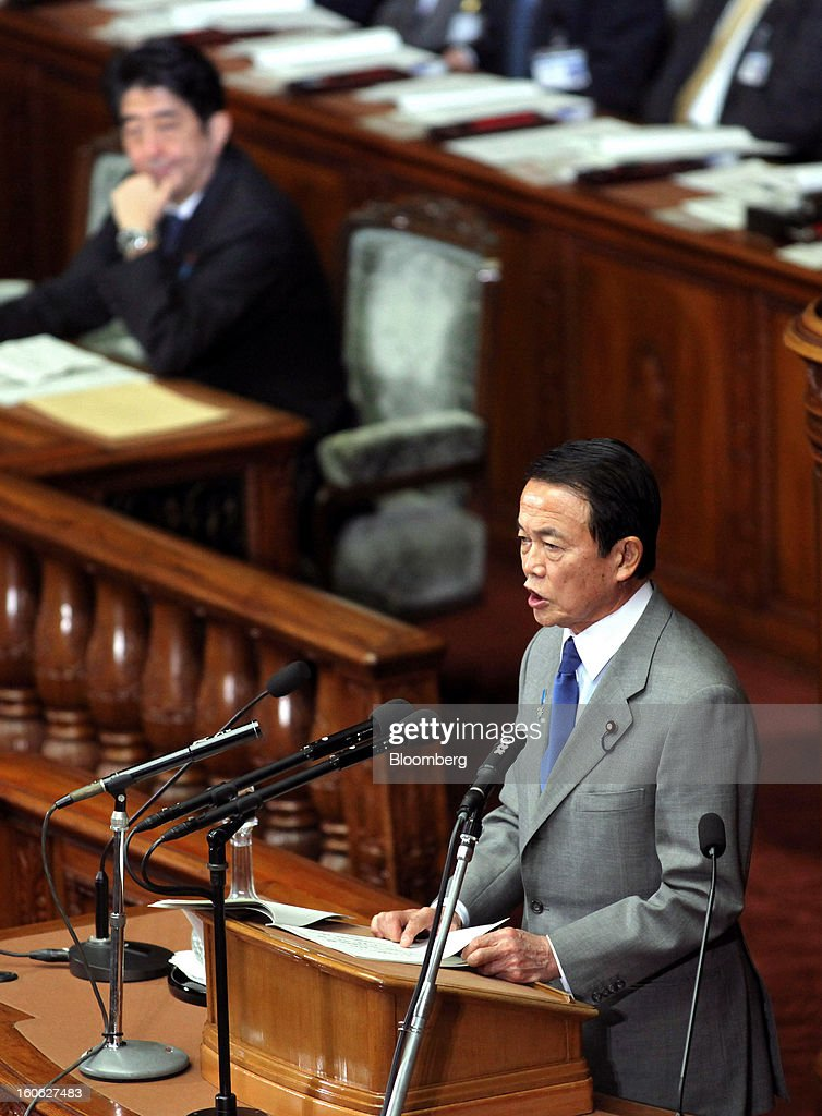 Taro Aso, Japan's deputy prime minister and finance minister, right, speaks as Shinzo Abe, Japan's prime minister, listens during a plenary session at the lower house of Parliament in Tokyo, Japan, on Monday, Feb. 4, 2013. Aso said Japan will keep monitoring the currency markets carefully. Photographer: Haruyoshi Yamaguchi/Bloomberg via Getty Images