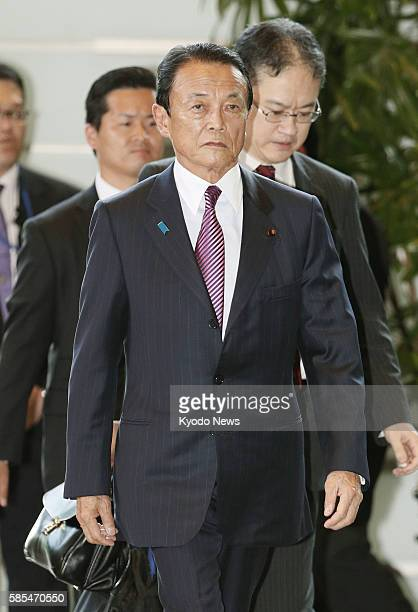 Taro Aso retained as finance minister in a Cabinet reshuffle enters the prime minister's office in Tokyo on Aug 3 prior to the attestation ceremony