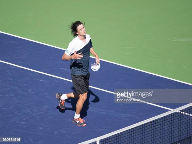 Taro Daniel jogs to the net to shake hands with Novak Djokovic after defeating Djokovic in the men's singles during the BNP Paribas Open on March 11...