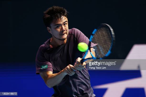 Taro Daniel of Japan plays a backhand in his Men's Singles first round match against Ramkumar Ramanathan of India on day one of the Singapore Tennis...