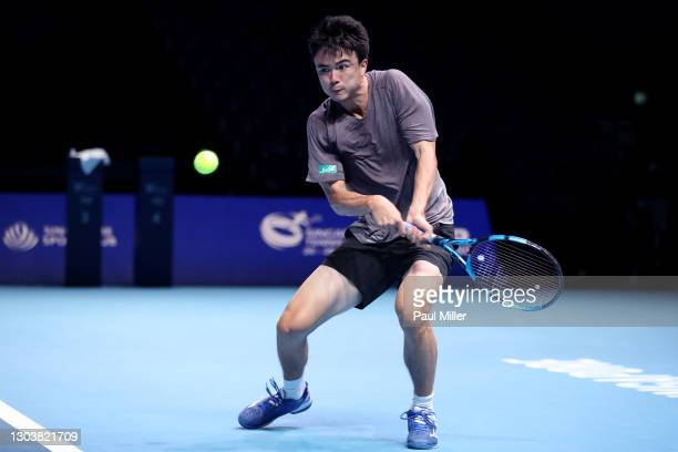Taro Daniel of Japan plays a backhand in his Men's Singles second round match against Marin Cilic of Croatia on day three of the Singapore Tennis...