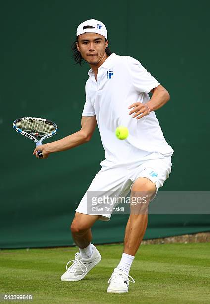 Taro Daniel of Japan plays a forehand during the Men's Singles first round match against Juan Monaco of Argentina on day two of the Wimbledon Lawn...