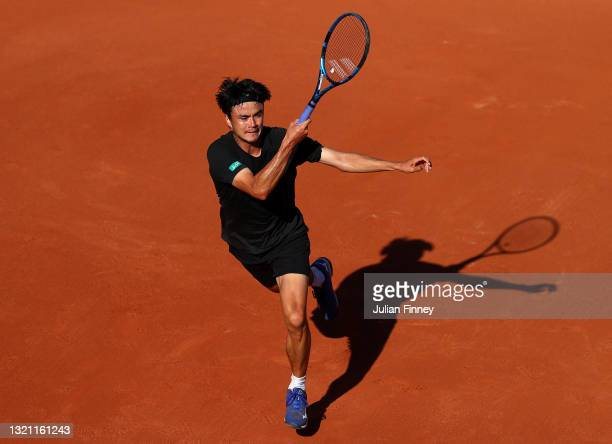 Taro Daniel of Japan plays a forehand in their mens first round match against Matteo Berrettini of Italy during day three of the 2021 French Open at...