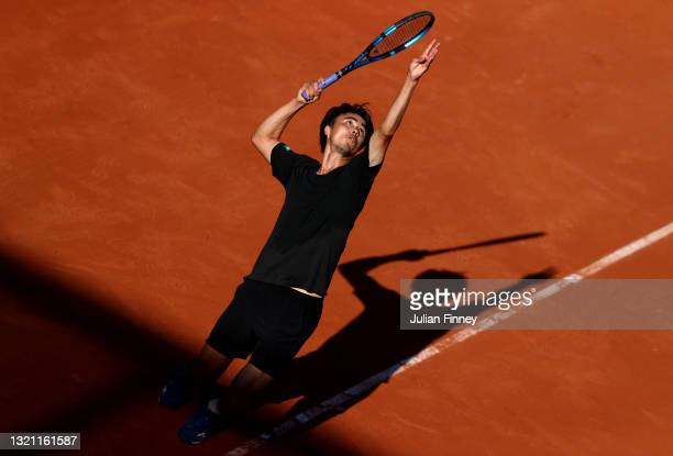 Taro Daniel of Japan serves in their mens first round match against Matteo Berrettini of Italy during day three of the 2021 French Open at Roland...