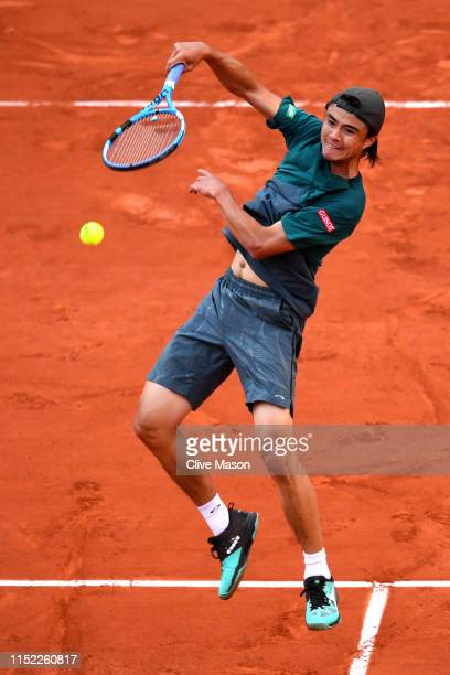 Taro Daniel of Japan volleys during his mens singles first round match against Gael Monfils of France during Day three of the 2019 French Open at...