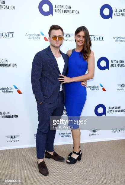 "Taron Egerton and Emily Thomas attends the first ""Midsummer Party"" hosted by Elton John and David Furnish to raise funds for the Elton John Aids..."