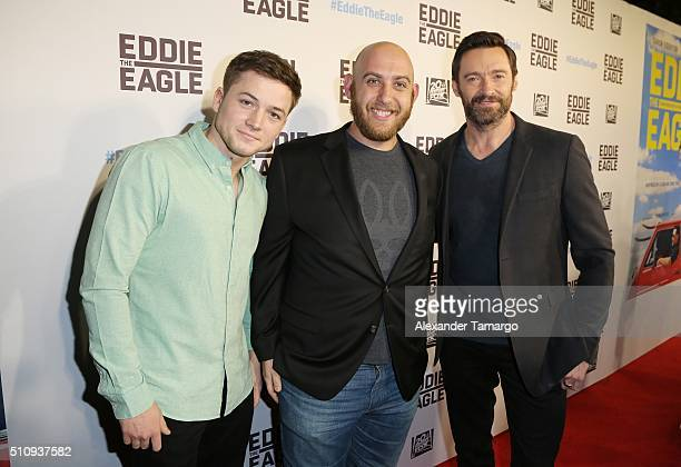 Taron Egerton and Hugh Jackman pose with a social influencer at the premiere of the film Eddie the Eagle at Regal South Beach on February 17 2016 in...