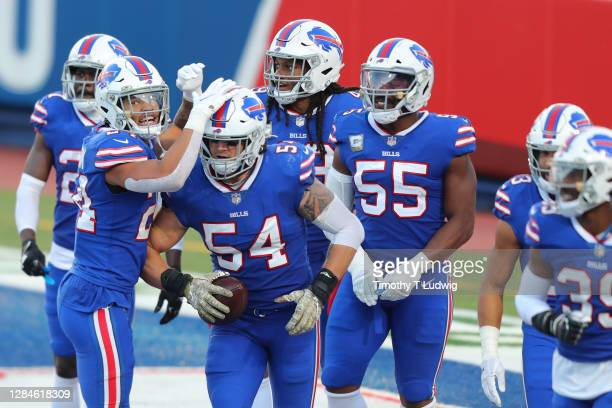Taron Johnson and A.J. Klein of the Buffalo Bills celebrate Klein's fumble recovery with teammates during the second half against the Seattle...