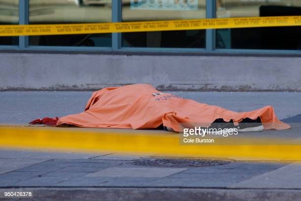 A tarp covers an unidentiified body on Yonge St at Finch Ave after a van plowed into pedestrians on April 23 2018 in Toronto Ontario Canada A suspect...