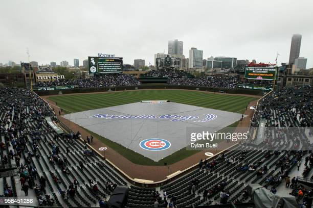 A tarp covers the field during a rain delay before the game between the Chicago White Sox and the Chicago Cubs at Wrigley Field on May 12 2018 in...