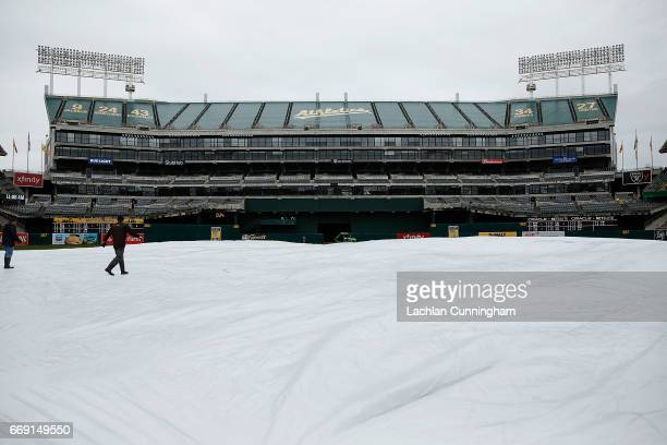 Tarp covers the infield as rain falls before the game between the Houston Astros and the Oakland Athletics at Oakland Alameda Coliseum on April 16,...