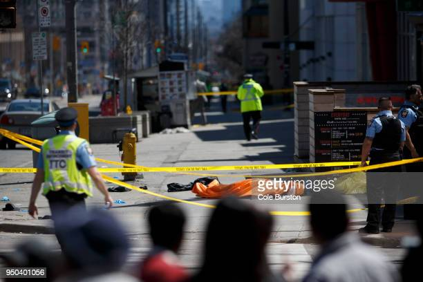 A tarp lays on top of a body on Yonge St at Finch Ave after a van plowed into pedestrians on April 23 2018 in Toronto Canada A suspect is in custody...