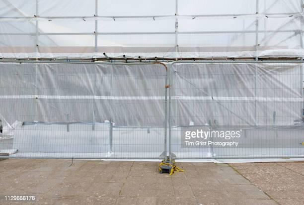 tarpaulin on scaffolding at construction site - tarpaulin stock pictures, royalty-free photos & images