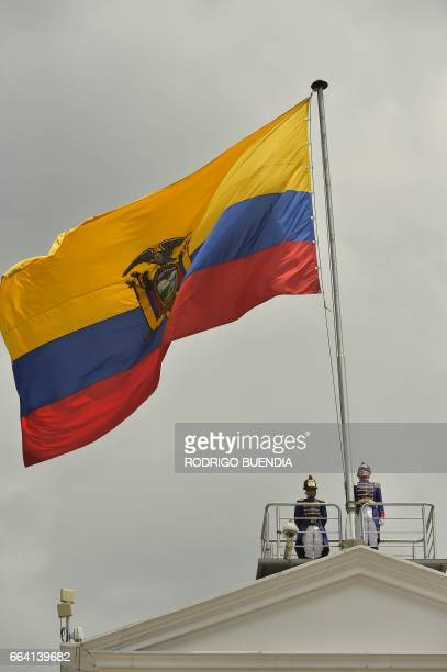 Tarqui grenadiers members of the presidetial escort rise Ecuador's national flag during the exchange of guard ceremony at the Carondelet presidential...