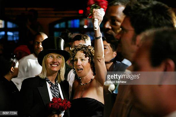 Tarra Berlegeay cheers as her partner Monica McCready looks on during a symbolic mass gay wedding celebrated by more than 100 samesex couples on June...