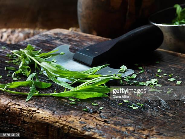 Tarragon, whole and chopped, mezzaluna on vintage chopping board