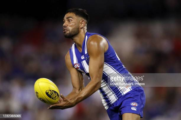 Tarryn Thomas of the Kangaroos handpasses the ball during the 2021 AFL Round 03 match between the North Melbourne Kangaroos and the Western Bulldogs...