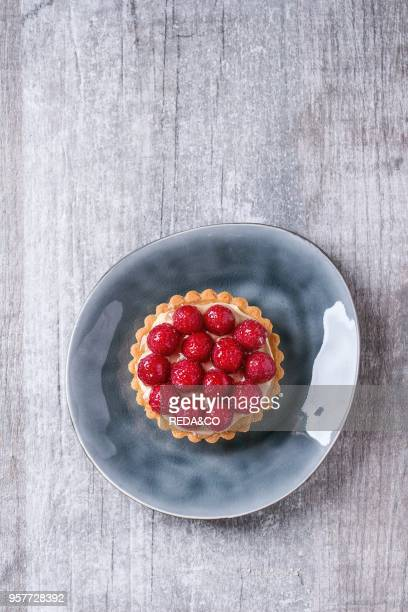 Tartlet with custard and fresh glazed raspberries served on gray ceramic plate over white wooden surface Top view