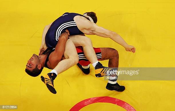 Tarvi Thomberg of Estonia is flipped by Hamsa Yerlikaya of Turkey in the men's GrecoRoman wrestling 84 kg qualification round on August 24 2004...