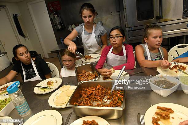 Taryn Bowman middle in gray tshirt and white apron serves herself some spicy turky and yam taco mix after she and the other girls prepared the entire...