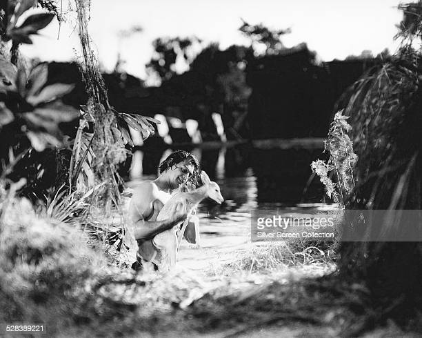 Tarzan played by American swimmer and actor Johnny Weissmuller saves a young deer in a scene from 'Tarzan Escapes' directed by Richard Thorpe 1936