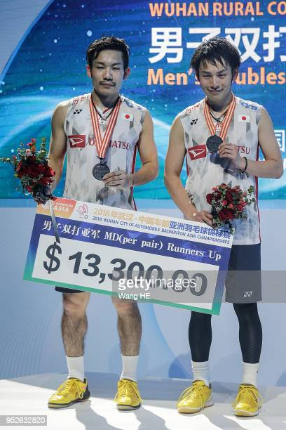 Taseshi Kamura and Keigo Sonda of Japan pose with silver medals on the podium after runners up the men's doubles final match against Li JUnhui and...