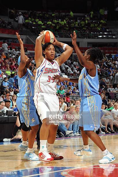 Tasha Humphrey of the Detroit Shock looks to pass the ball under pressure against Quianna Chaney and Jia Perkins of the Chicago Sky during the WNBA...