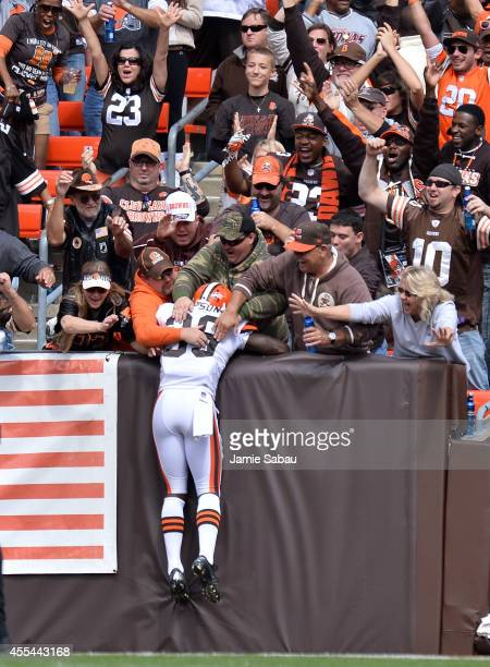 Tashaun Gipson of the Cleveland Browns celebrates his interception return for a touchdown with fans during the second quarter against the New Orleans...