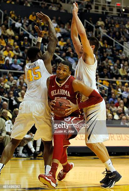 TaShawn Thomas of the Oklahoma Sooners drives to the basket against Elijah Macon and Nathan Adrian of the West Virginia Mountaineers during the game...