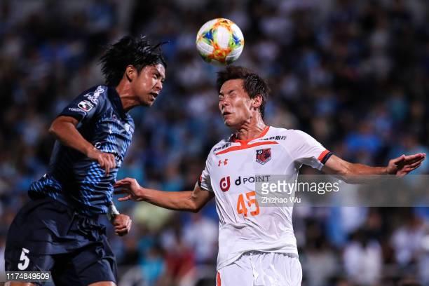 Tashiro Masakazu of Yokohama FC competes for the ball with Kushibiki Kazuki of Omiya Ardija during the J.League J2 match between Yokohama FC and...