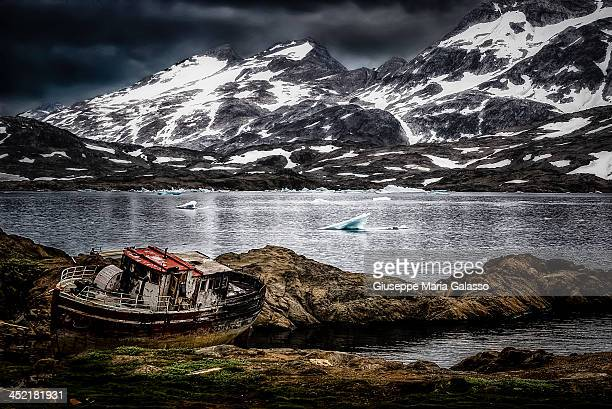 CONTENT] Tasiilaq Eastern Greenland A wrecked boat stranded on the rocks with arctic mountains in background
