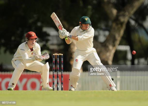 Tasmania player George Bailey looks to play a shot as Queensland keeper Jimmy Peirson looks on during day two of the Sheffield Shield Final match...